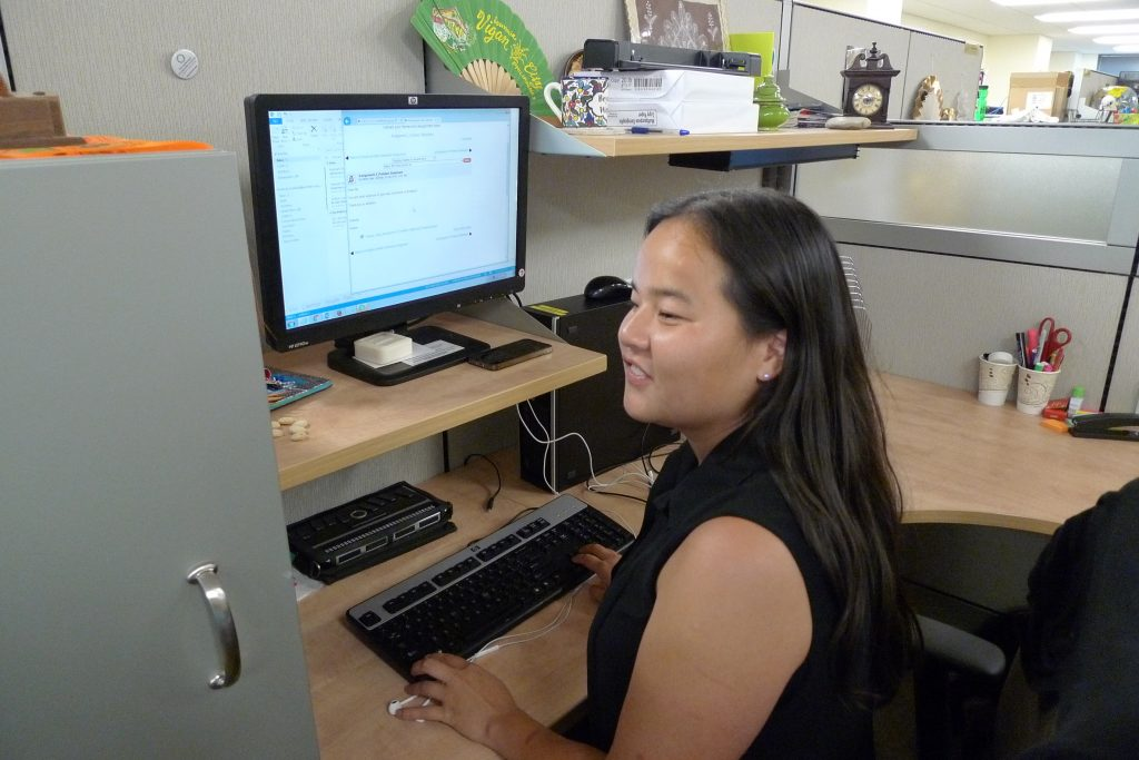 An intern sits in front of her computer at her host organization.